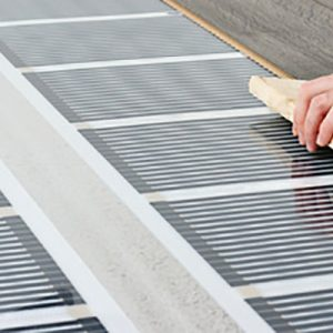 man installing laminate floor over infrared carbon heating syste